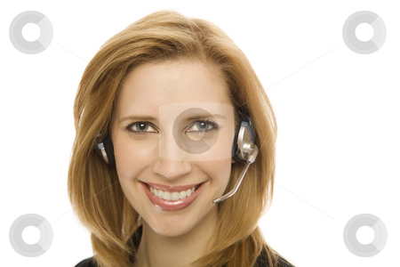 Businesswoman with a headset stock photo, Businesswoman in a suit happily uses a headset by Rick Becker-Leckrone