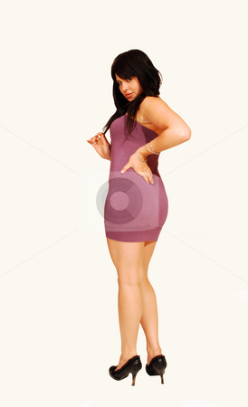 Woman looking back. stock photo, A young pretty woman standing in a studio and looking back shooing her nice round butt, for white background. by Horst Petzold