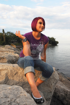 Girl sitting on lakeshore. stock photo, An red hair girl in jeans sitting on the shore of lake Ontario at sunset. by Horst Petzold