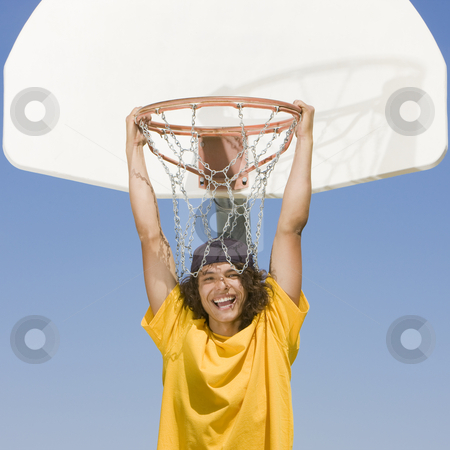 Teen biy hangs from hoop stock photo, A teen basketball player hangs from a basketball hoop and smiles by Rick Becker-Leckrone