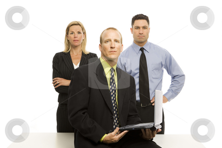 Businesspeople near desk stock photo, Three business people stand near a desk by Rick Becker-Leckrone