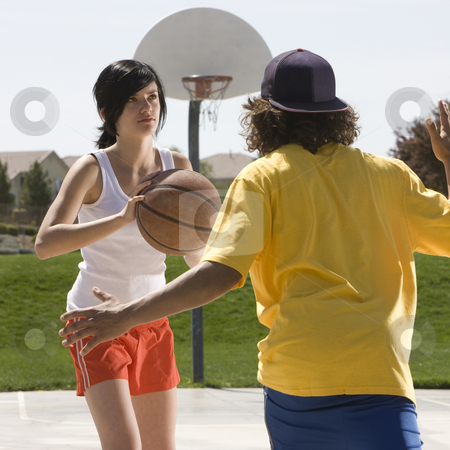 Teens play basketball stock photo, Two teens play basketball in a court by Rick Becker-Leckrone