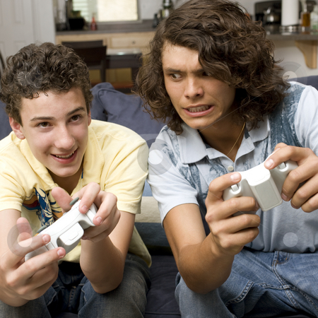 Two guys play video games stock photo, Two guys play videogames on a couch by Rick Becker-Leckrone