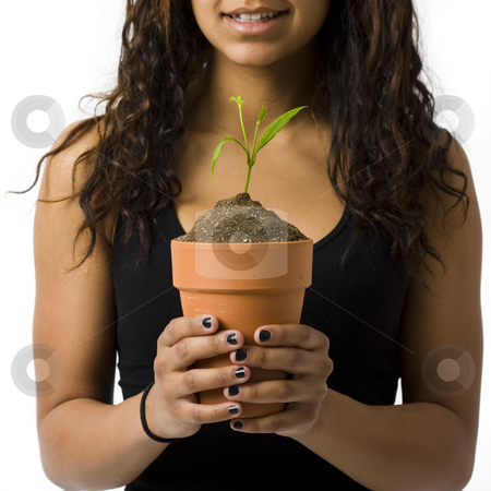 Girl with potted plant smiles stock photo, A girl with a potted plant smiles by Rick Becker-Leckrone