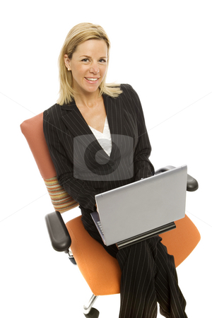 Businesswoman in chair with laptop stock photo, Businesswoman in a suit sits in a chair with a laptop smiling by Rick Becker-Leckrone