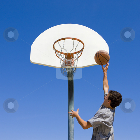 Teen jumps and shoots basketball stock photo, A teen boy jumps and shoots a basketbal by Rick Becker-Leckrone