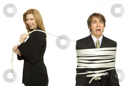 Businesswoman ties up coworker stock photo, Businesswoman ties up man with rope and smiles by Rick Becker-Leckrone