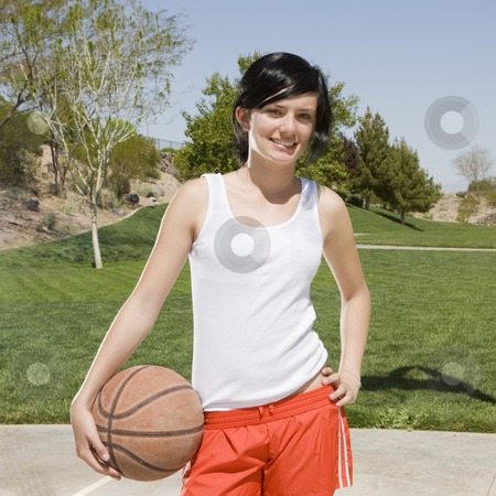 Teen girl with basketball stock photo, A teen girl with a basketball hangs out at a park by Rick Becker-Leckrone