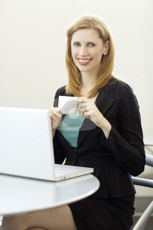 Businesswoman with coffee and laptop stock photo, Businesswoman holds a cup of coffee near her laptop by Rick Becker-Leckrone