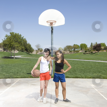Teens hang out at basketball court stock photo, Two teens hang out at a basketball court by Rick Becker-Leckrone