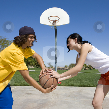Couple plays basketball stock photo, Two teens play basketball at a park by Rick Becker-Leckrone