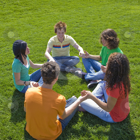 Five teens hold hands stock photo, Five teens hold hands while sitting in a park by Rick Becker-Leckrone