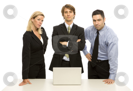 Businesspeople stand confidently stock photo, Three business people stand near a table with a laptop by Rick Becker-Leckrone