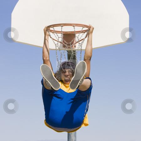 Teen hangs from basketball hoop stock photo, An excited teen hangs from a basketball hoop by Rick Becker-Leckrone