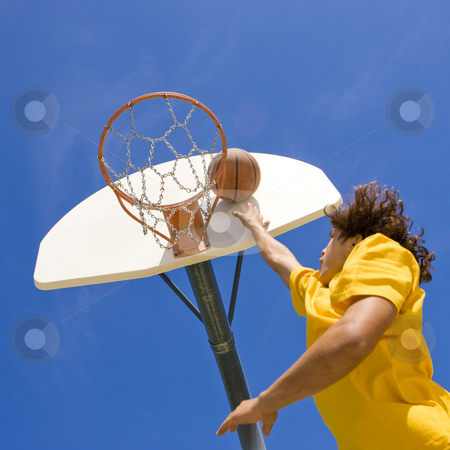 Basketball player jumps and shoots stock photo, A teen basketball player jumps and shoots by Rick Becker-Leckrone