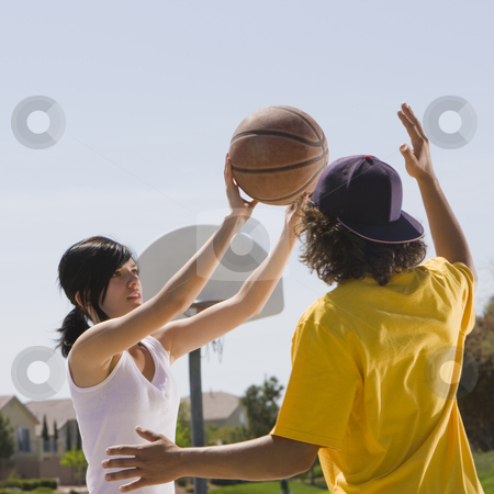 Two teens play basketball stock photo, Two teens play basketball in a park by Rick Becker-Leckrone