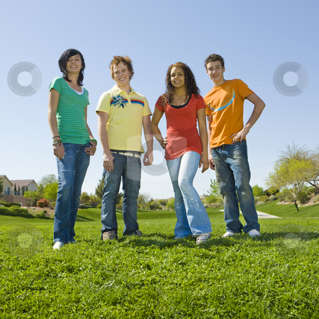 Group of teens in park stock photo, Group of teens stan in green grass by Rick Becker-Leckrone