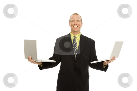 Businessman with laptop stock photo, Businessman in a suit stands holding two laptops by Rick Becker-Leckrone