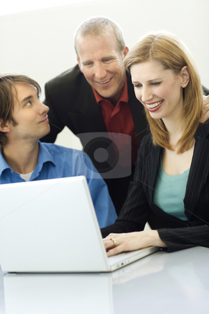 Three workers talk stock photo, Three workers talk while using a laptop by Rick Becker-Leckrone