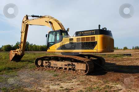 Heavy excavator. stock photo, An yellow heavy excavator sitting on an field to begin construction of an industrial site. by Horst Petzold