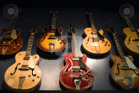 Vintage Guitars stock photo, A wall with vintage guitars hanging on display. by Todd Arena
