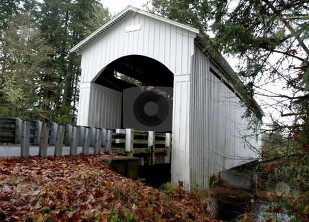 White covered bridge over river stock photo, White wooden covered bridge over river by Jill Reid