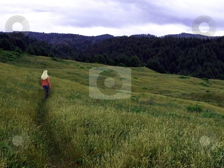 Girl on grassy hillside stock photo, Girl walks along a path on a grassy hillside by Jill Reid