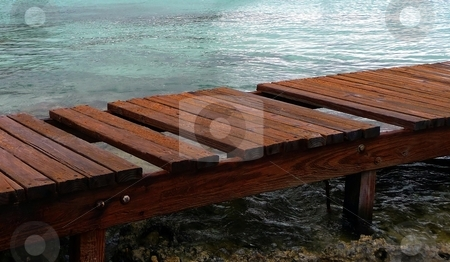 Wooden pier into the ocean stock photo, Close-up of a wooden pier going into the water by Jill Reid