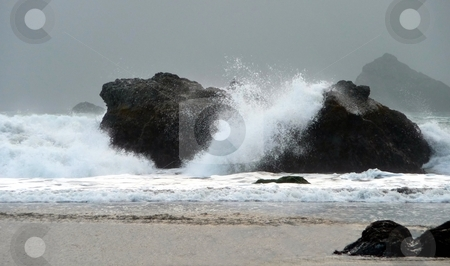 Waves crash on stormy beach stock photo, A winter storm brings heavy waves crashing on rocks along an Oregon beach by Jill Reid