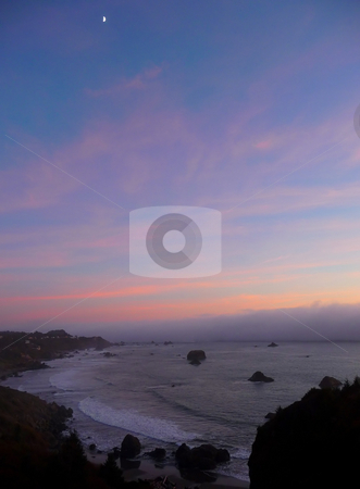 Moon rises over ocean fog bank stock photo, A moon rises in the sky over the ocean as a fogbank rolls in at sunset by Jill Reid
