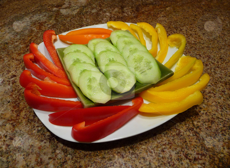Sweet bell peppers and cucumbers stock photo, Plate with an arrangement of red, yellow and orange bell pappers and sliced cucumbers by Jill Reid