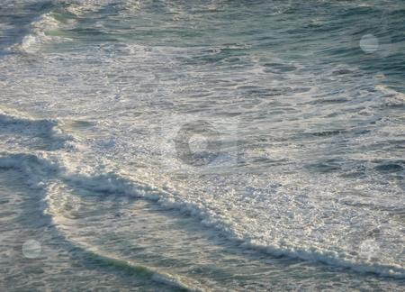 Foaming gentle waves along the coast 250A stock photo, Foamy gentle waves roll into shore, lit by the sun by Jill Reid