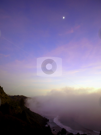 Moon over foggy beach stock photo, A wave of fog rolls in over an Oregon coastline with a moon in the sky by Jill Reid