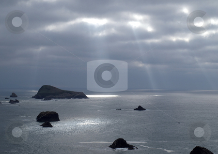 Sunlight from the heavens stock photo, Sunlight beams through the clouds and onto the ocean by Jill Reid