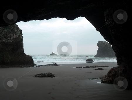 Footprints through a beach cave stock photo, A footprint trail leads in and out of a beach along a sandy coast by Jill Reid