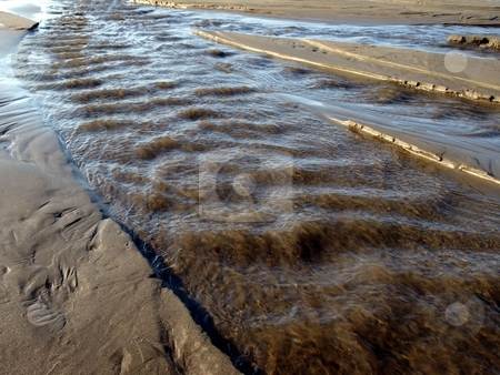 Rushing riptide on the beach stock photo, A river swells with water and rushes along a sandy beach by Jill Reid