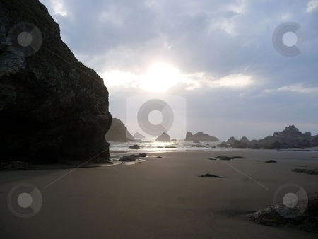 Afternoon sun glares on a rocky beach stock photo, The afternoon sun glares through the clouds onto a sandy beach by Jill Reid