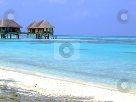 Suspended tropical chalets stock photo, Chalets suspended over bright blue water on a tropical island by Chris Alleaume