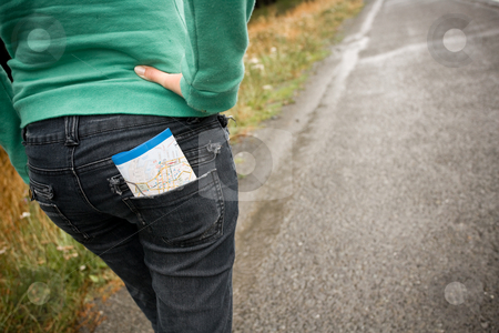 Lost stock photo, A girl walks along a road with a map in her pocket by Angus Benham