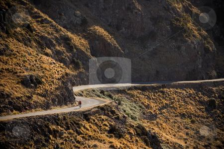 Cycle road stock photo, A cyclist on a winding road by Angus Benham