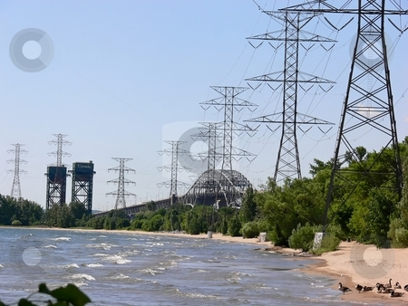 Two bridges and hydro tower  stock photo, A lift bridge and a highway bridge with power lines on the shore of lake Ontario on the beach. by Horst Petzold