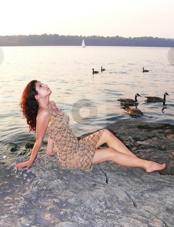 Lady on the lake in sunset  stock photo, An lovely young lady sitting on a big rock on the lake relaxing by sunset. by Horst Petzold