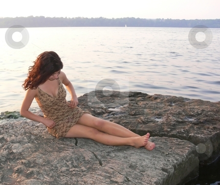 Lady on the lake in sunset   stock photo, An lovely young lady sitting on a big rock on the lake and try to fix her dress on a nice sunset. by Horst Petzold