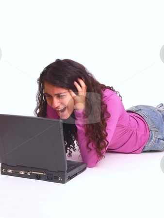 Crazy girl   stock photo, A young girl laying on the floor with her nice long curly dark hair working on the laptop and is surprised what she sees. On white background. by Horst Petzold