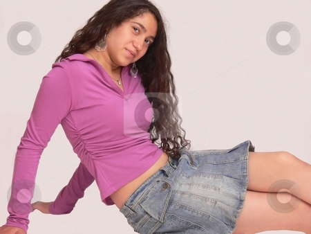 Young girl sit on the floor  stock photo, An young girl in an mini skirt is sitting on the floor with her long curly dark hair and looking in the camera. On white background. by Horst Petzold
