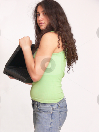 Surprised girl   stock photo, An surprised looking girl standing in her jeans and try to hide the laptop. Her long dark curly hair is framing her face. On white background. by Horst Petzold