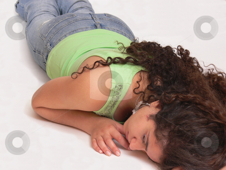 The sleeping girl  stock photo, An sleeping girl, laying in jeans on the floor on her stomach and her  long dark curly hair is running down her back, on white background. by Horst Petzold