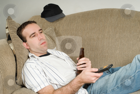Male With Beer Watching TV stock photo, A young man holding a beer while changing channels with a tv remote control by Richard Nelson