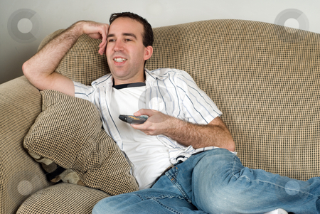 Relaxing After Work stock photo, A young man watching tv and relaxing after a day at work by Richard Nelson