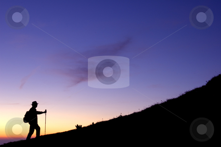 Dawn climber stock photo, High in the mountains a walker climbs a ridge, silhouetted in the pre-dawn light. by Alistair Scott